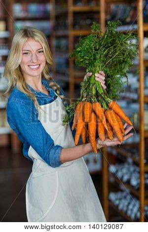 Portrait of smiling staff holding bunch of carrots in organic section of supermarket