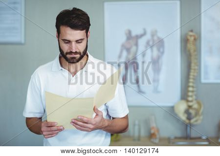Physiotherapist reading a file in clinic