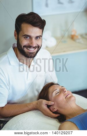 Smiling physiotherapist giving head massage to a woman in clinic