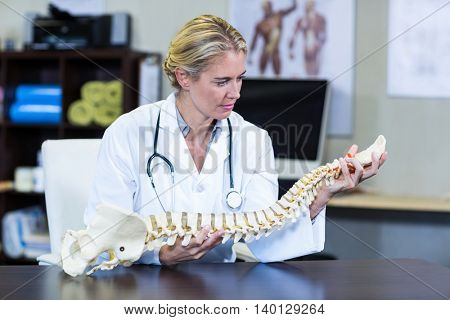 Thoughtful physiotherapist holding a spine model in clinic