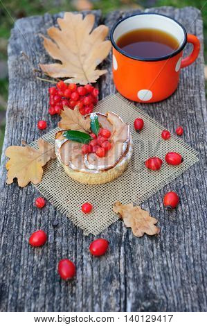 Romantic autumn still life with basket cake, cup of tea, rowan berries and leaves at wooden board
