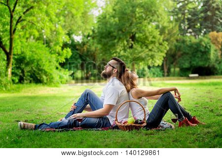 Couple sitting on a picnic blanket enjoying the peace and nature and their time together