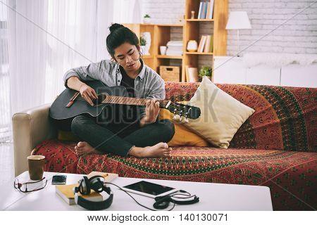 Vietnamese creative man playing guitar at home