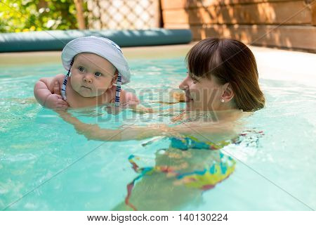 Mom and son with panama swimming in the pool