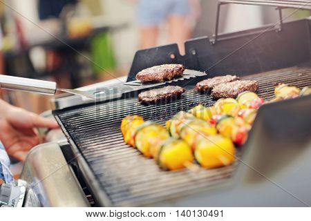Closeup of grilled shashliks and hamburgers on grate