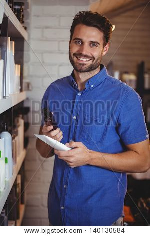 Portrait of smiling male hair dresser selecting shampoo from shelf at a salon