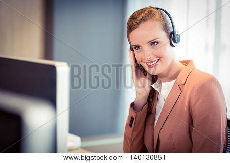Businesswoman talking on headphones at office
