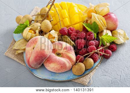 Fresh and ripe tropical fruit board including mango, longan and peaches