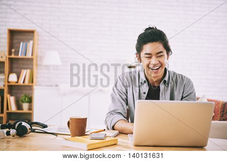 Portrait of cheerful young man working on laptop at home