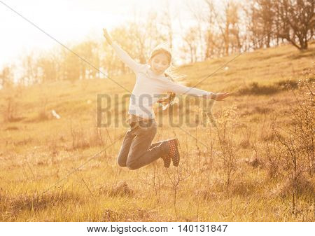 smiling little girl jumping on sunlight in countryside on a hill