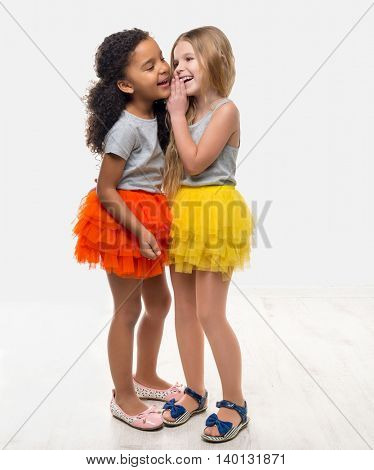 two little pretty girls in colorful skirts talking and laughing isolated on white background