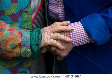 Hands. Close-up.Old man and old woman holding hands. Walk. True love.