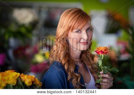 Female florist holding a rose flower in the flower shop