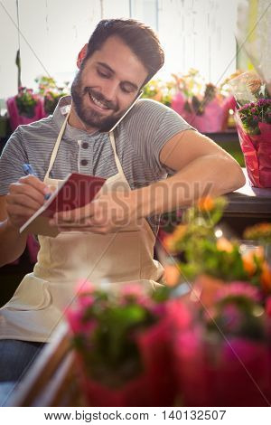 Male florist noting order in dairy while talking on mobile phone at his flower shop