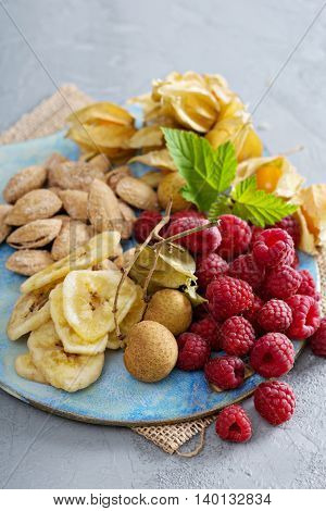 Fruit and nuts snack board including almonds, raspberry, dried banana, gooseberry and longan
