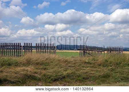 Damaged fence with mountains in the background