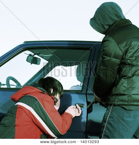 Two crime guys breaking door of a car