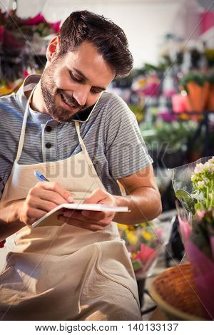 Male florist noting order in diary while talking on mobile phone at his flower shop