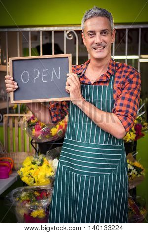Portrait of male florist holding open sign on slate at his flower shop