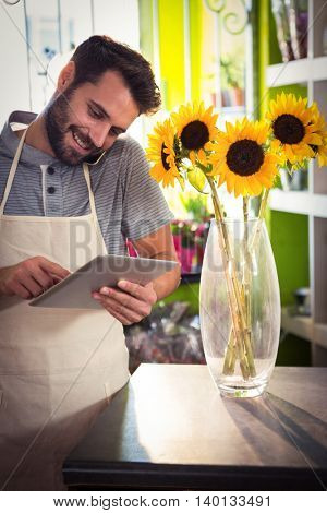 Male florist talking on mobile phone while using digital tablet at his flower shop