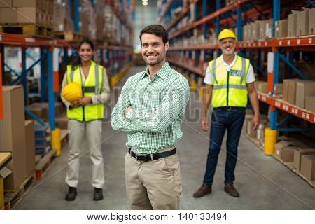 Focus on manager is posing with crossed arms in front of his workers in a warehouse