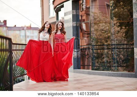Portrait of two fashionable girls at red evening dress posed background mirror window of modern building