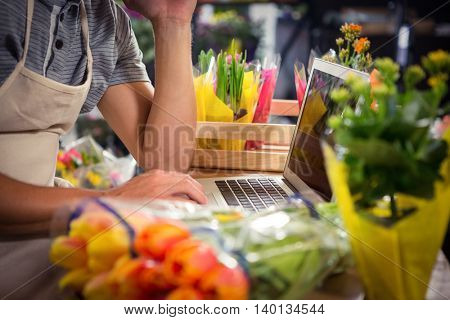Mid section of male florist using laptop at his flower shop