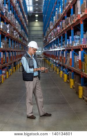 View of worker is using a tablet in front of shelves in a warehouse