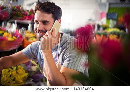 Male florist talking on mobile phone at his flower shop