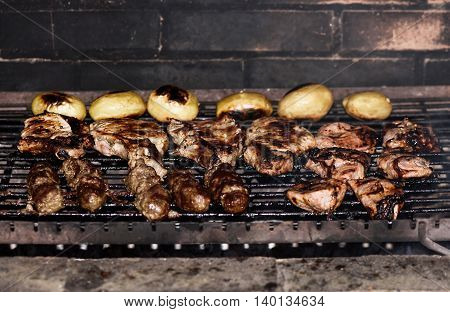 Photo of meet and potatoes on grill shallow focus.