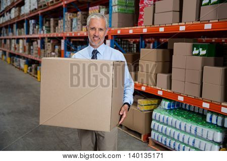 Worker holding boxes in a warehouse
