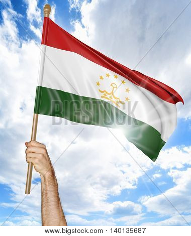 Person's hand holding the Tajikistan national flag and waving it in the sky, 3D rendering