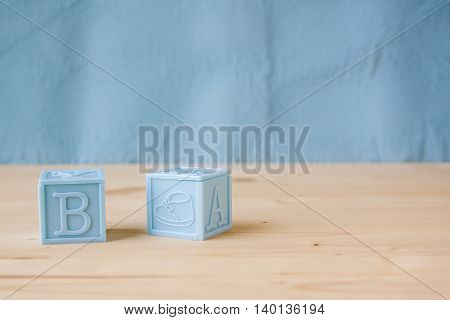 Blue Baby Blocks on a Wooden and Blue Background