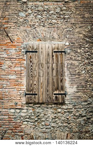 Old wooden window closed and stone and brick wall.