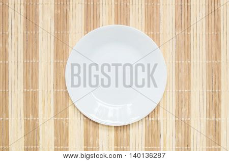 Closeup white ceramic dish on wood mat textured background at the center on dining table in top view with copy space