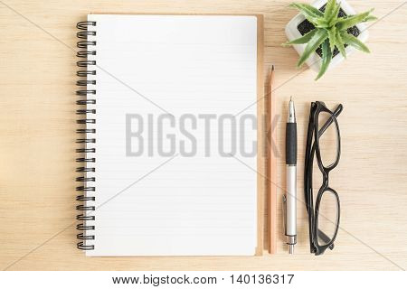 Desk above Top view of open spiral notebook with brown pencil pen black eye glasses and small plant pot on wooden background