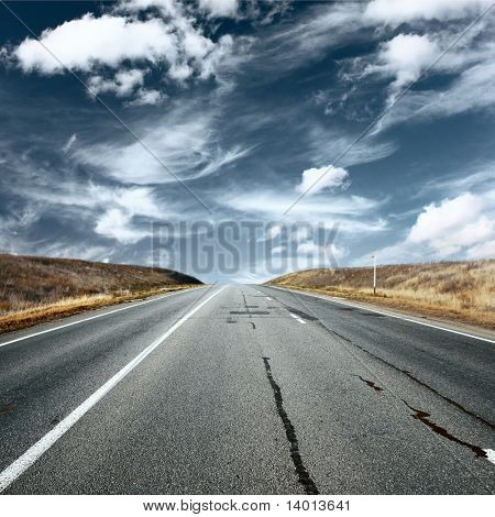 Asphalt road under fluffy clouds