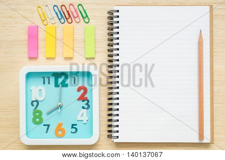 Desk above table top view of stationery items - clock notebook notepad pencil sticky notes paper clips on wooden background