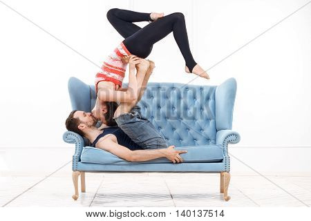 Young Beautiful Man And Woman Practicing Acroyoga Doing Excercise And Kissing On Blue Sofa In White Interior