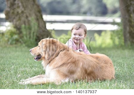Little girl playing with dog at the park