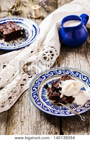 Brownie with ice cream and a black currant on rough shabby wooden boards