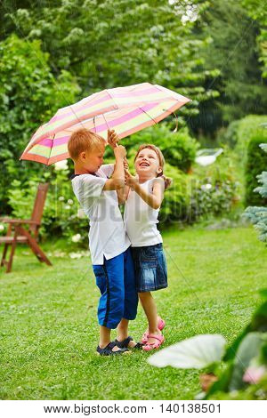 Two children standing under an umbrella in rain in a garden
