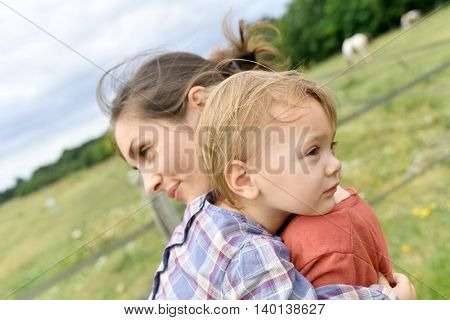 Mother and daugther cuddling in countryside