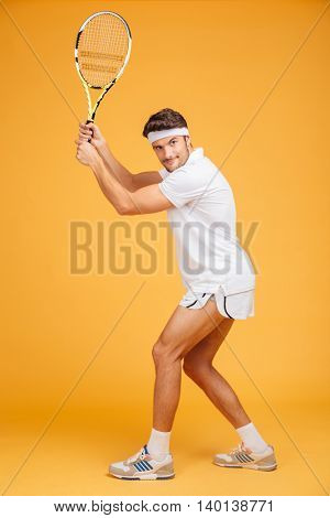 Full length of attractive young man tennis player standing and playing tennis over yellow background