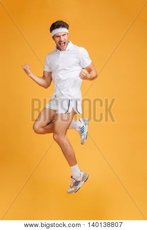 Happy handsome young sportsman shouting and jumping in the air over yellow background