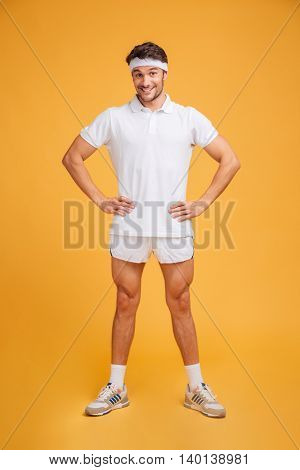 Full length of joyful amusing young sportsman standing with hands on hips over yellow background