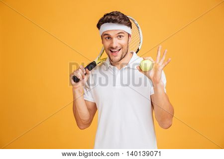 Cheerful young man tennis player holding ball and racket over yellow background