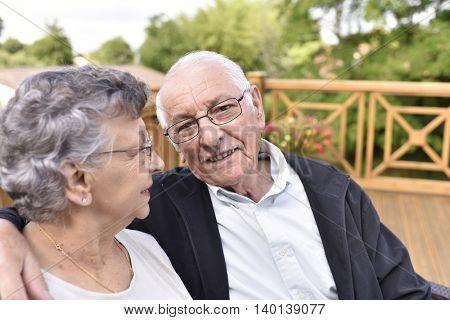 Portrait of elderly couple relaxing outside senior home