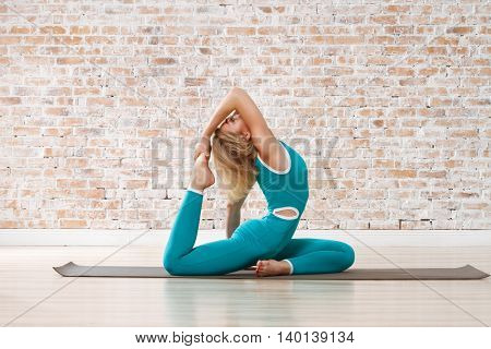 Young Beautiful Woman Practicing Yoga Doing Excercise On Brick Wall Ball Background