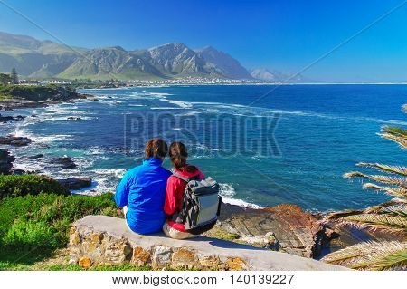 Happy couple looking at beautiful ocean view in Hermanus, romantic vacation in South Africa